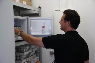 Ein Mann holt kleine Glasflaschen aus einem offenen Tresor