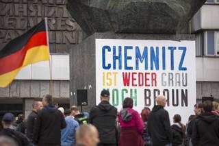 Auf dem Karl-Marx-Monument in Chemnitz klebt ein Plakat, davor versammeln sich Menschen