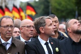 Drei Männer stehen in vorderster Front einer Demonstration, der Mittlere trägt eine weiße Rose