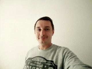 Selfie eines Mann vor seiner Wohnzimmerwand