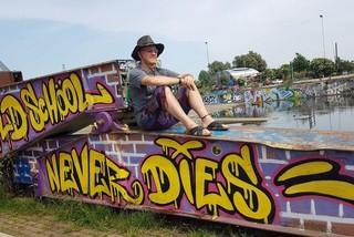 Ein Mann sitzt mit Shorts und Sonnenhut auf einer Hafenmauer