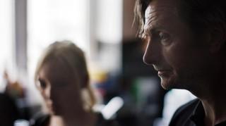 Ein Mann schaut ernst und gedankenverloren, im Hintergrund sitzt eine junge Frau, den Blick gesenkt
