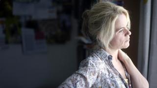 Eine Frau blickt gedankenverloren aus dem Fenster