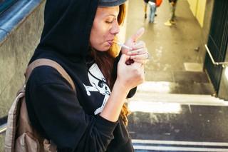 Eine Frau – Rucksack, Kapuzenpulli, lange Haare, Lippen-Piercings – zündet sich eine Zigarette an