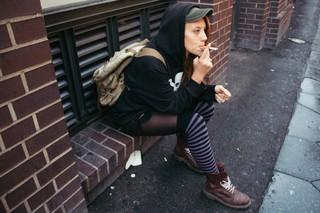 Kaya hockt in einem Mauersims und raucht, sie trägt Boots und gestreifte Kniestrümpfe