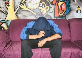Ein Mann sitzt auf einer Couch vor einer mit Graffiti besprühten Wand und zieht die Kapuze seiner Trainingsjacke vors Gesicht