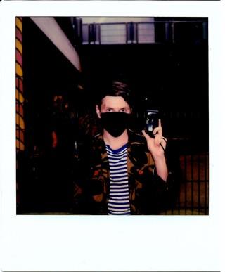 Ein Polaroid auf dem ein junger Mann mit Maske vor Mund und Nase eine Analogkamera hochhält