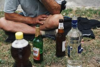 Ein Mann sitzt vor einer Auswahl an Getränken im Gras