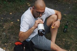 Ein junger Mann hockt im Gras und trinkt Eistee