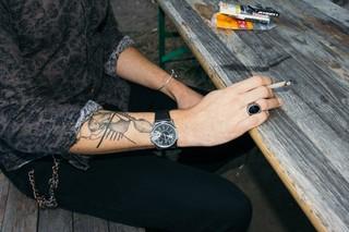 Ein Mann sitzt auf einer Bierbank, sein Gesicht ist nichts zu sehen, eine Zigarette in der Hand seines tätowierten Arms