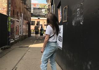 Eine junge Frau steht auf der Strasse und dreht ihr Gesicht weg