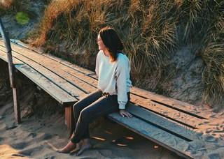 Eine Frau sitzt am Strand und blickt in die Sonne