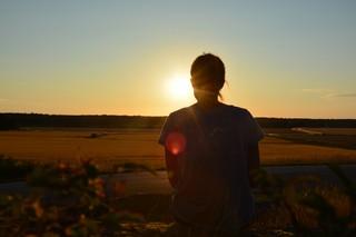 Eine Frau beobachtet einen Sonnenuntergang