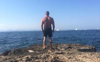 Ein muskulöser Mann steht in Badehose am Meer