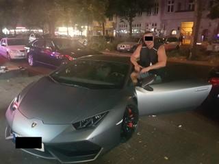 Der Mann posiert mit einem silbergrauen Lamborghini