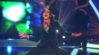Ein Mann mit langen Haaren und ausgefallener Krawatte singt auf einer Showbühne