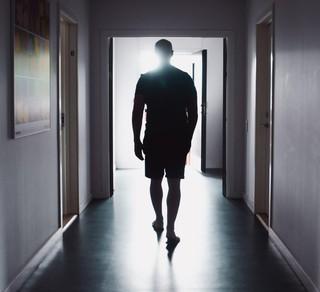 Ein Mann steht in einem kargen Flur mit mehren Türen