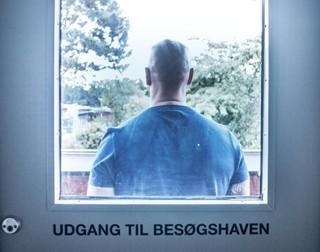 Ein Mann steht in Gefängniskleidung vor einer Tür mit Sichtfenster
