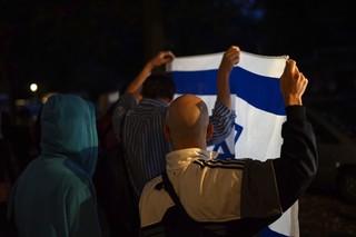 Zwei Männer, den Rücken zur Kamera, halten im Dunklen eine Israel-Fahne hoch