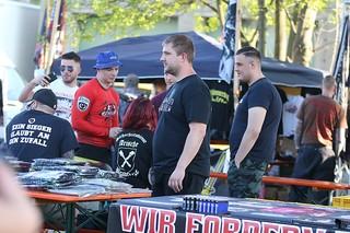 Eine Gruppe von Männer und Frauen an Bierbänken, auf einem T-Shirt steht