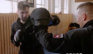 Zwei Männer stehen in Polizeiuniformen in einer Turnhalle, einer hält eine Pratze hoch, der andere boxt hinein