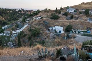 Ein Hügel durchzogen von Höhleneingängen und einem kurvigen Weg