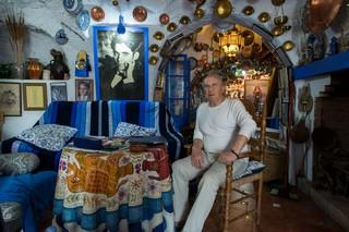 Ein alter Herr sitzt am Esstisch in seiner vollständig dekorierten Höhle