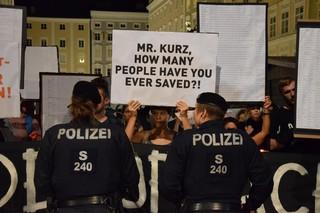 Eine Demonstrantin hält zwischen zwei Einsatzkräften ein Schild hoch: