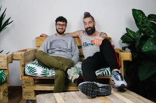 Zwei junge Männer in legeren Klamotten sitzen auf einem Sofa aus Holzpaletten