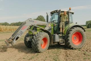 Der Bauer steht an der Fahrertür des Traktors