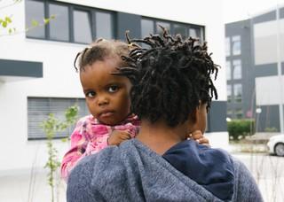 Ein Kind sitzt auf dem Arm seiner Mutter und schaut in die Kamera