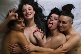 Billede af fire nøgne kvinder, der ligger og smiler i en seng