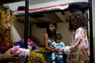 Alejandra Agrinzones, 22, receives clothing donations for her children during her stop at the Holy Spirit Refuge in Tunja.