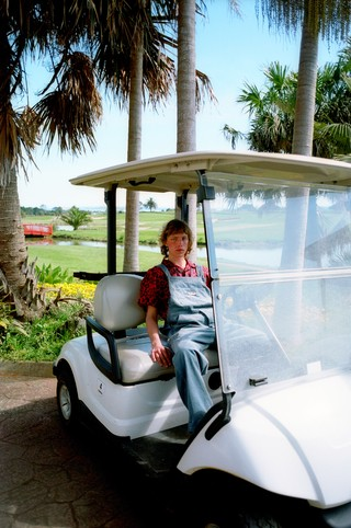 A man wearing overalls on a golf cart