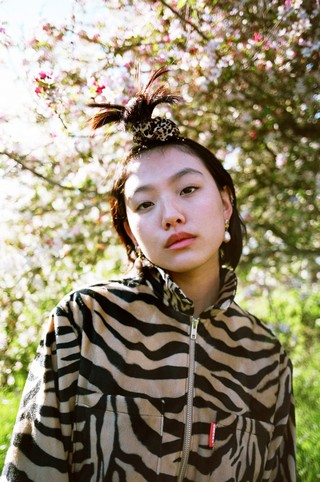 A girl in a patterned jacket in front of a blossoming tree.