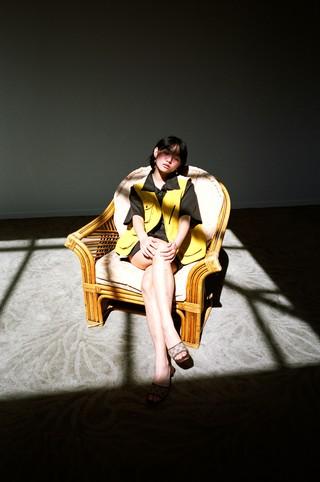A girl sits on a wicker chair under a sun lit window