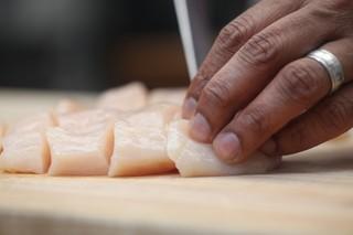 hands cutting raw chicken