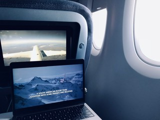 a laptop playing the movie Alive on an airplane tray table
