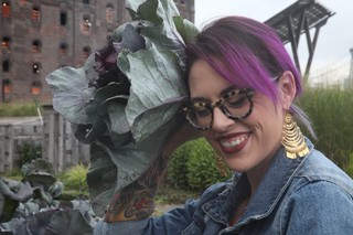 Claudette Zepeda-Wilkins holding red cabbage as if it is a flower in her hair