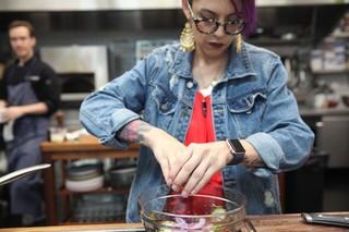 Claudette Zepeda-Wilkins squeezing lemon juice over cabbage slaw
