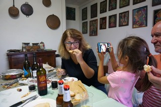 Woman eating cheese while a child takes her picture.