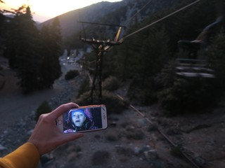 the movie 'Frozen' playing on a cell phone screen. In the background is a ski lift