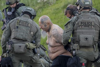 Federal agents arrest a person with Vagos motorcycle gang tattoos as a suspect in a 2011 murder of a rival gang leader. Early Friday morning June 16, 2017 federal agents detained many people after serving arrest and search warrants at home being operated as a rehab center, in Moreno Valley targeting a biker gang suspected of drug trafficking as well as murder.