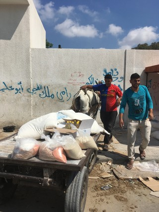 1540314956303-mutasem-in-the-blue-shirt-at-the-UNRWA-food-ditribution-center