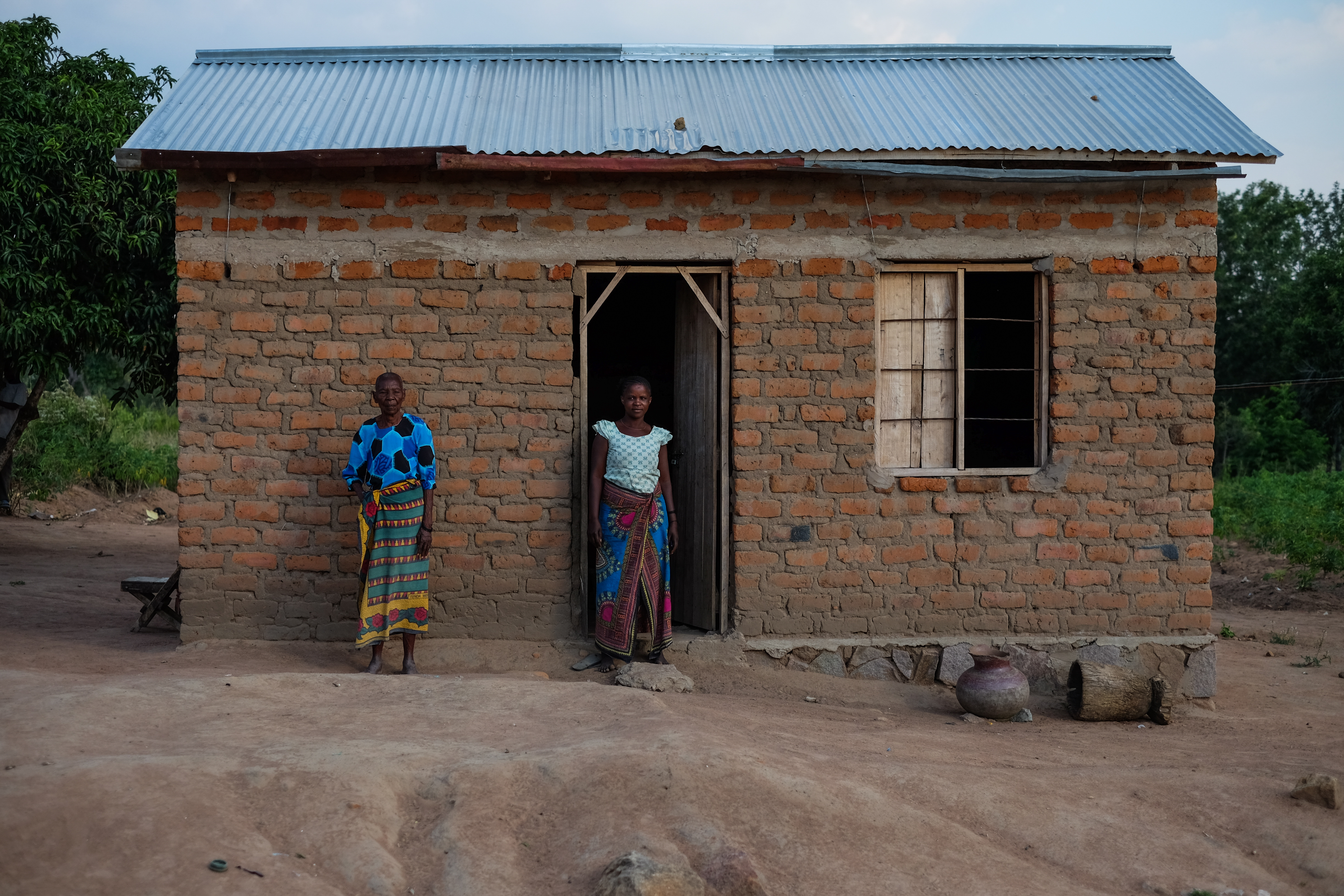 Women in nyumba ntobhu marriage pose outside their house