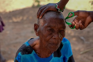 Old woman has her hair cut