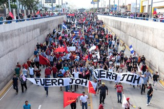 Protesters against Juan Orlando Hernandez march down a street