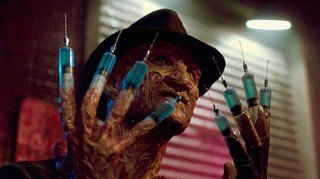 Freddy Kreuger holds up his hands in front of his face, each finger replaced by a syringe full of blue liquid