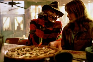 Freddy Krueger leans on a diner counter with his fist on his chin, smiling at a worried looking woman seated next to him