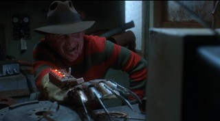 a smiling Freddy Krueger leans forward over a desk toward a TV, his knife glove augmented with an electronic device